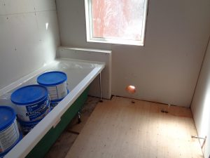 Bathroom walls boarded ready for the tiles. The bath fitted and silicon sealed to the wall to create a water tight seal.