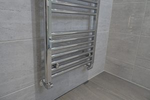 Chrome towel warmer fitted to ensuite wall with chrome heating pipes