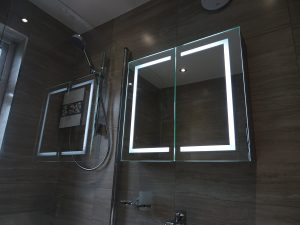 Bathroom fitted with LED mirror cabinet above basin