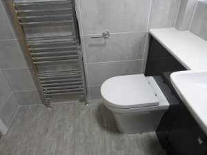 Tiled Bathroom with chrome towel warmer and fitted furniture